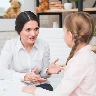 Retrato, de, um, sorrindo, femininas, psicólogo, conversa com menina, em, escritório