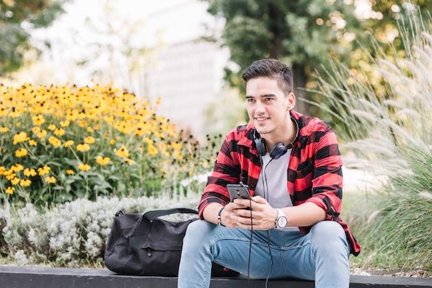 Retrato, de, um, sorrindo, homem jovem, com, cellphone