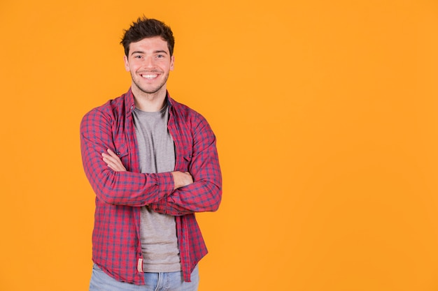 Retrato, de, um, sorrindo, homem jovem, com, seu, braços cruzaram, olhando câmera