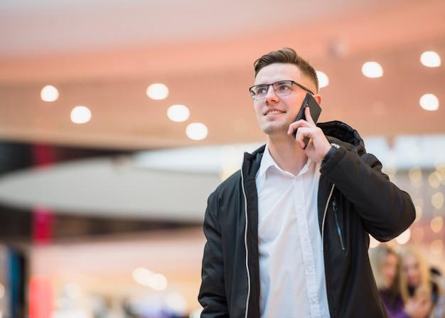 Retrato, de, um, sorrindo, homem jovem, falando, ligado, a, smartphone