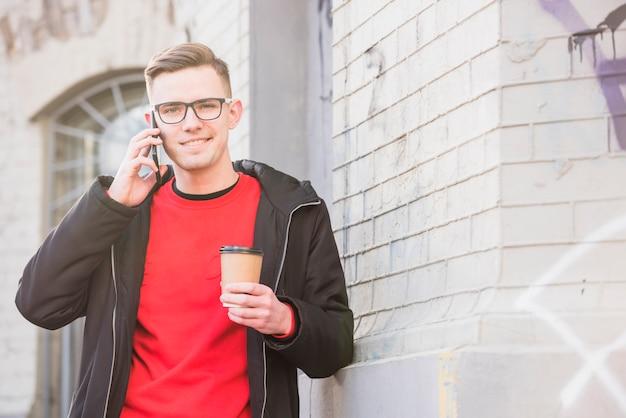 Retrato, de, um, sorrindo, homem jovem, falando telefone móvel, segurando, takeaway, café