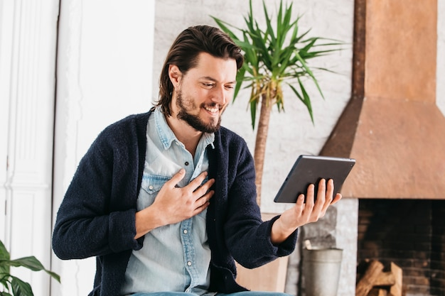 Retrato, de, um, sorrindo, homem jovem, fazendo, chamada vídeo, usando, tablete digital