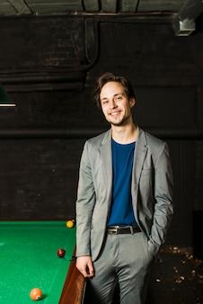 Retrato, de, um, sorrindo, homem jovem, posar, perto, piscina bilhar, em, clube