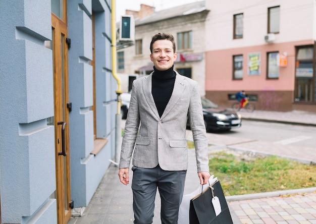 Retrato, de, um, sorrindo, homem jovem, segurando, bolsas para compras, andar, ligado, rua