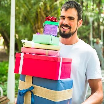Retrato, de, um, sorrindo, homem jovem, segurando, pilha presentes
