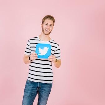 Retrato, de, um, sorrindo, homem jovem, segurando, twitter, ícone