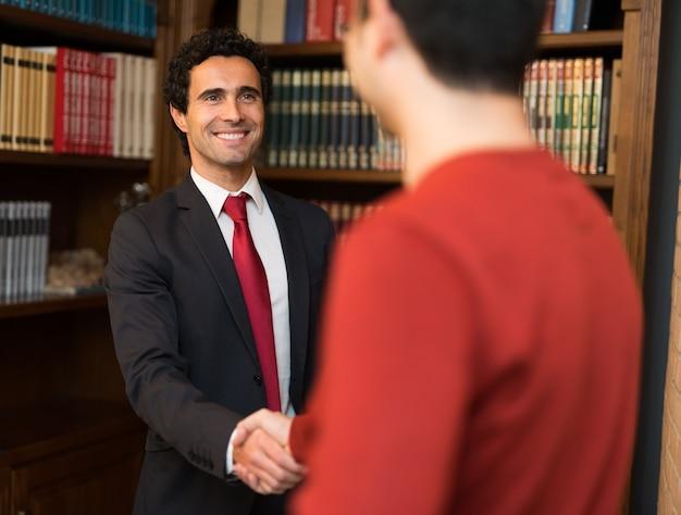 Retrato, de, um, sorrindo, homem negócios, dar, um, aperto mão, para, um, cliente