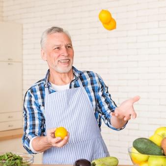 Retrato, de, um, sorrindo, homem sênior, juggling, inteiro, limões, enquanto, preparar, a, cozinha