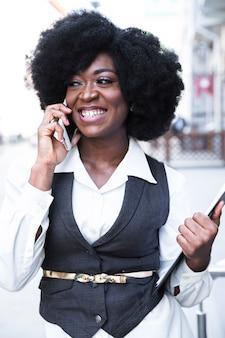 Retrato, de, um, sorrindo, jovem, africano, executiva, segurando clipboard, em, mão, falando telefone móvel