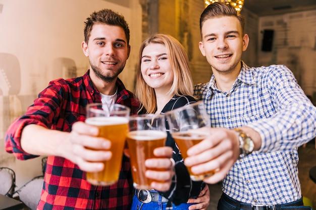 Retrato, de, um, sorrindo, jovem, amigos, brindar, a, copos cerveja