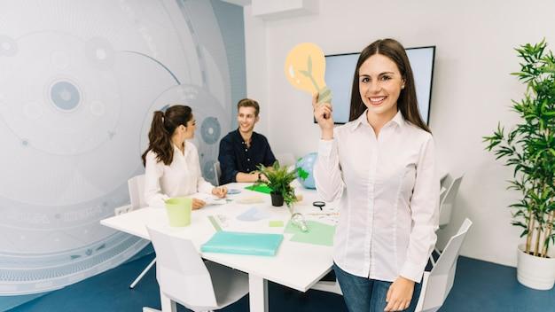 Retrato, de, um, sorrindo, jovem, executiva, com, bulbo leve, ícone, ficar, em, escritório
