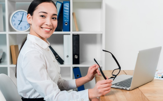 Retrato, de, um, sorrindo, jovem, executiva, segurando, óculos, em, mão, com, laptop, escrivaninha