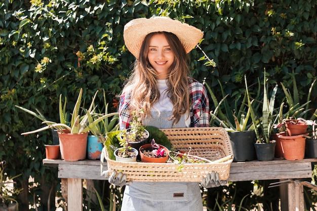 Retrato, de, um, sorrindo, jovem, femininas, jardineiro, segurando, potted, plantas, em, a, cesta