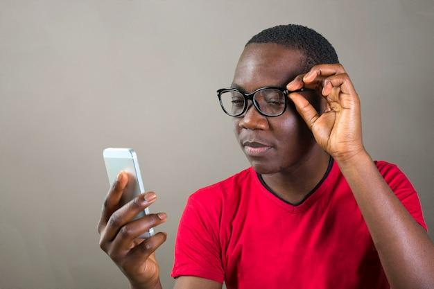 Retrato, de, um, sorrindo, jovem, homem africano, usando, smartphone