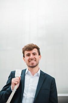 Retrato, de, um, sorrindo, jovem, homem negócios, contra, parede cinza