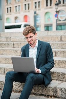 Retrato, de, um, sorrindo, jovem, homem negócios, sentar escada, usando computador portátil