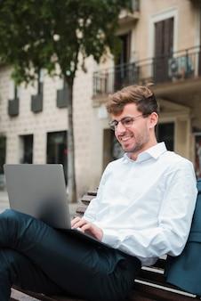 Retrato, de, um, sorrindo, jovem, homem negócios, usando computador portátil