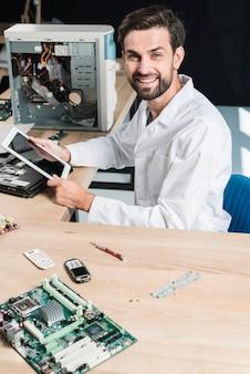 Retrato, de, um, sorrindo, jovem, macho, técnico, segurando, tablete digital