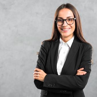 Retrato, de, um, sorrindo, jovem, mulher negócios fica, com, dela, braço cruzou, contra, parede cinza