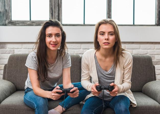 Retrato, de, um, sorrindo, jovem, par lésbica, sentar sofá, videogame jogo, com, joysticks