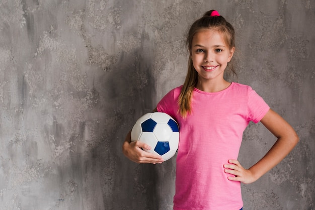 Retrato, de, um, sorrindo, loiro, menina, com, passe quadril, segurando, bola futebol, contra, parede cinza