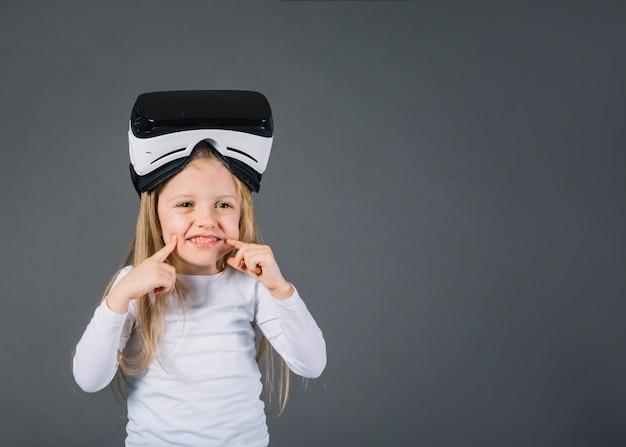 Retrato, de, um, sorrindo, loiro, menininha, com, virtual, realidade, óculos, ligado, cabeça, tocar, dela, bochechas