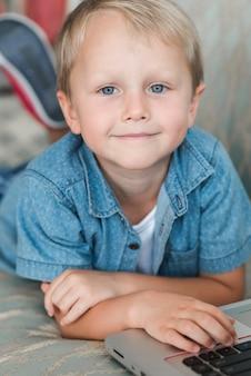 Retrato, de, um, sorrindo, loiro, menino, com, laptop