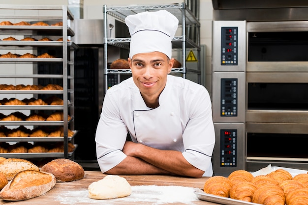 Retrato, de, um, sorrindo, macho jovem, padeiro, estar, atrás de, a, tabela, com, fresco, croissant, e, loaf pão