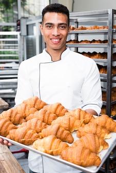 Retrato, de, um, sorrindo, macho, padeiro, segurando bandeja, de, croissant cozido