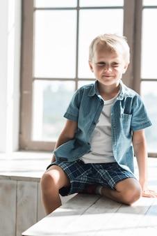 Retrato, de, um, sorrindo, menino sentando, perto, a, janela