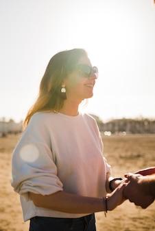 Retrato, de, um, sorrindo, mulher jovem bonita, segurando mão, de, dela, namorado, ligado, dia ensolarado, em, praia
