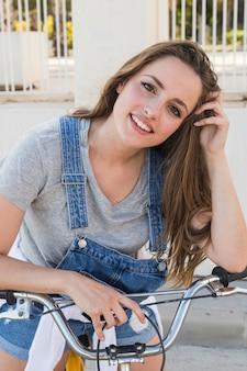 Retrato, de, um, sorrindo, mulher jovem, com, bicicleta