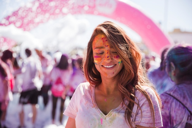 Retrato, de, um, sorrindo, mulher jovem, com, holi, cor, rosto