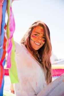 Retrato, de, um, sorrindo, mulher jovem, com, pintado, rosto, com, holi, cor