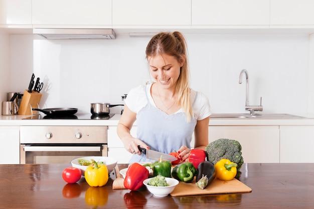 Retrato, de, um, sorrindo, mulher jovem, corte, a, legumes frescos, com, faca, ligado, tabela madeira