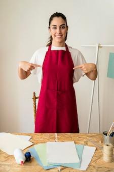 Retrato, de, um, sorrindo, mulher jovem, dedos apontando, em, dela, avental vermelho