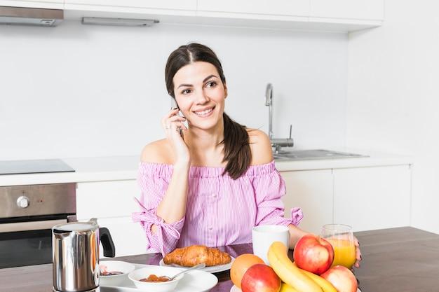 Retrato, de, um, sorrindo, mulher jovem, falando telefone móvel, tendo, pequeno almoço