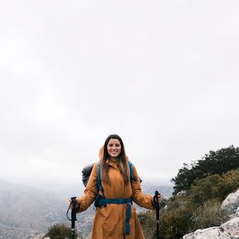 Retrato, de, um, sorrindo, mulher jovem, ficar, auge, montanha, segurando, vara hiking