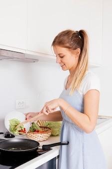 Retrato, de, um, sorrindo, mulher jovem, preparar, a, legumes, cozinha
