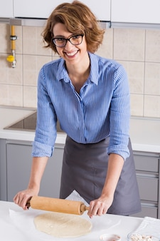 Retrato, de, um, sorrindo, mulher jovem, rolando, a, massa pizza