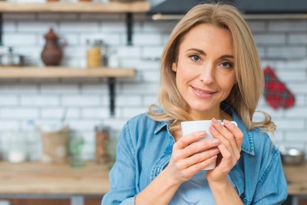 Retrato, de, um, sorrindo, mulher jovem, segurando, branca, xícara café, em, mão