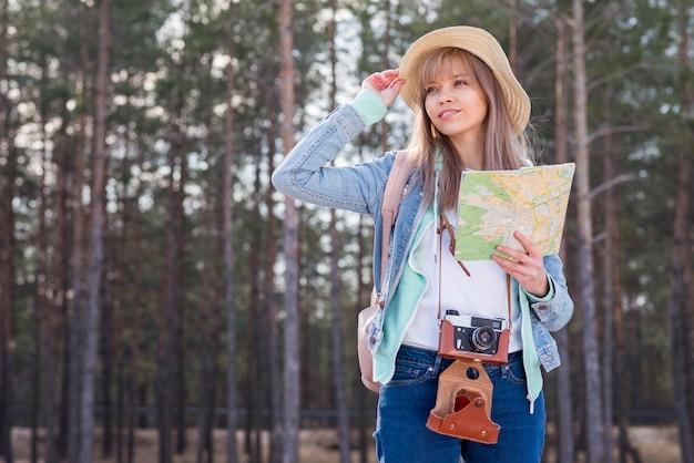 Retrato, de, um, sorrindo, mulher jovem, segurando, mapa, em, mão