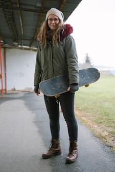 Retrato, de, um, sorrindo, mulher jovem, segurando, skateboard, em, mão