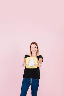 Retrato, de, um, sorrindo, mulher jovem, segurando, snapchat, ícone