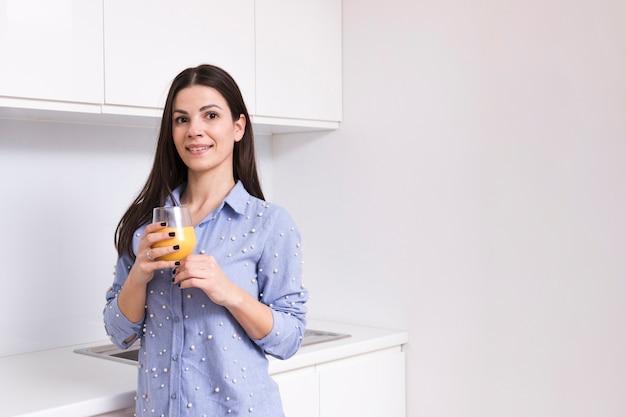Retrato, de, um, sorrindo, mulher jovem, segurando, suco, vidro, em, mão, olhando câmera