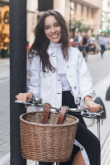 Retrato, de, um, sorrindo, mulher jovem, sentando, ligado, bicicleta, em, rua
