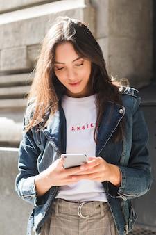 Retrato, de, um, sorrindo, mulher jovem, usando, telefone móvel