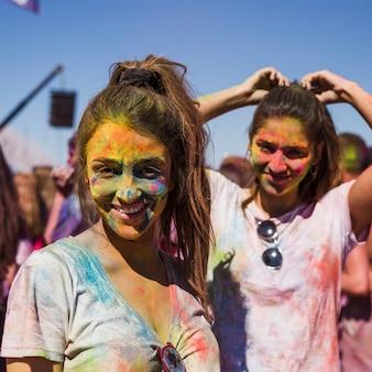 Retrato, de, um, sorrindo, mulheres jovens, com, holi, cores, ligado, dela, rosto, olhando câmera