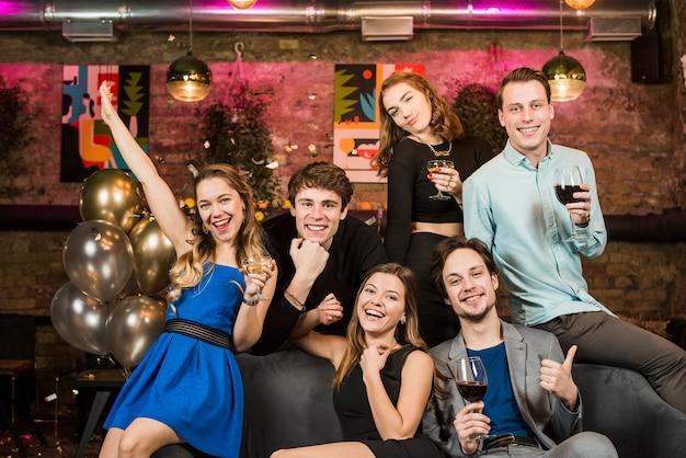 Retrato, de, um, sorrindo, pares jovens, segurando, copos de vinho, desfrutando, partido
