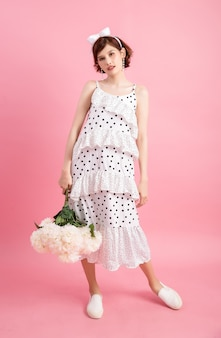 Retrato, de, um, sorrindo, playful, cute, mulher segura, flores, isolado, ligado, cor-de-rosa